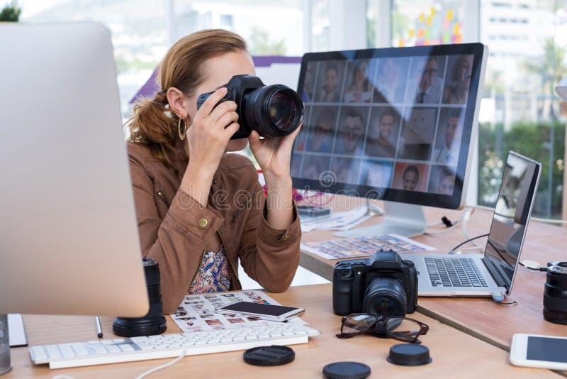Weibliche Exekutive, die ein Foto von der Digitalkamera macht stockfotos