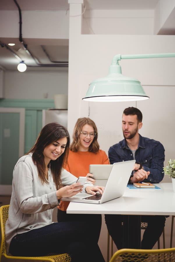 Weibliche Exekutive, die Handy und Laptop im Büro verwendet stockbild