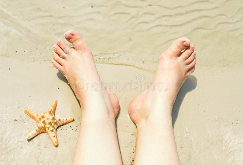 Weibliche Füße auf einem sandigen Strand