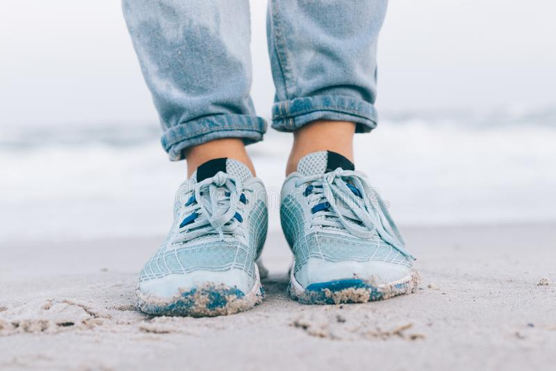 Weibliche Füße in den nassen Jeans und in den Turnschuhen lizenzfreies stockfoto