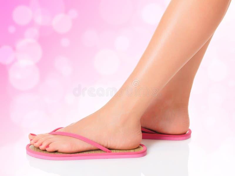 Weibliche Füße in den rosafarbenen Sandelholzen lizenzfreies stockfoto