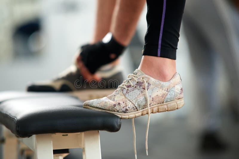 Weibliche Füße in den Turnschuhen im Turnhallenabschluß oben stockfoto