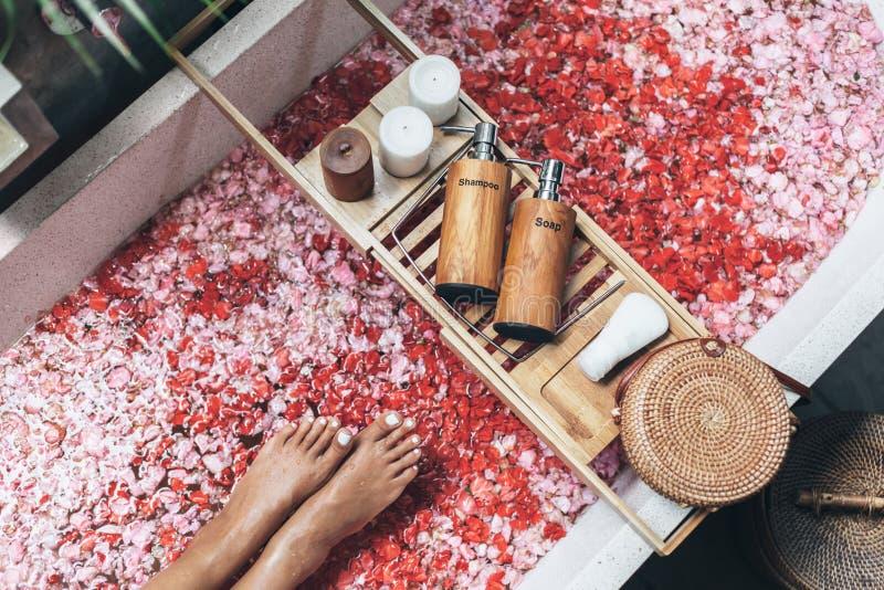 Weibliche Füße in der Badewanne mit den Blumenblumenblättern und den Schönheitsprodukten auf hölzernem Behälter stockfotografie