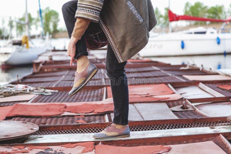 Weibliche Füße in der modernen Hose und in den Schuhen auf dem Pier stockfotos