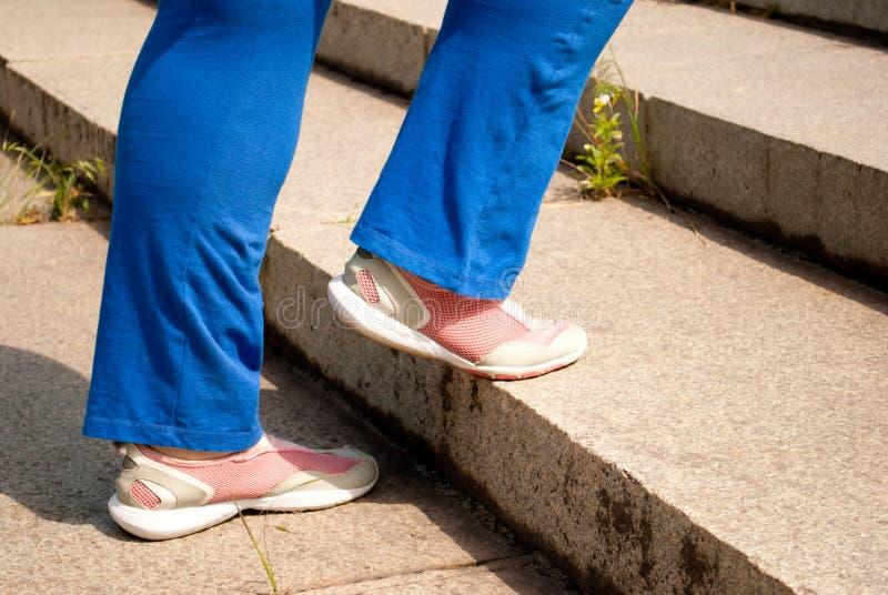 Weibliche Füße des Sportathleten berichtigen das verbogene Bein lizenzfreie stockfotografie