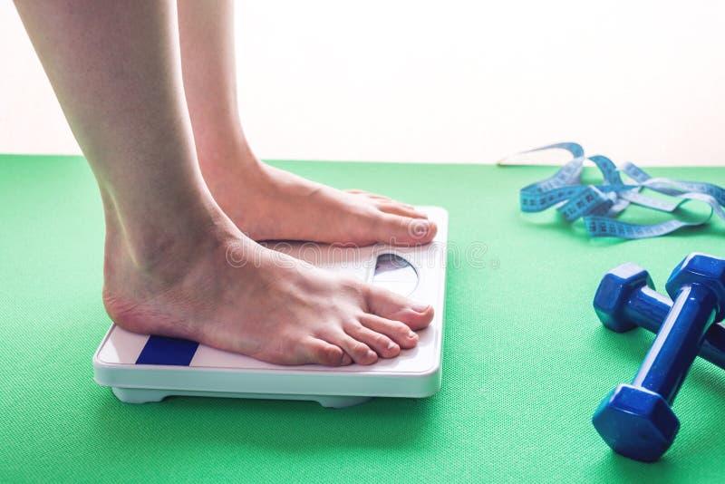 Weibliche Füße, die auf mechanischen Skalen, Dummköpfen und messendem Band stehen Konzept des Abnehmens und des Gewichtsverlusts lizenzfreie stockfotos