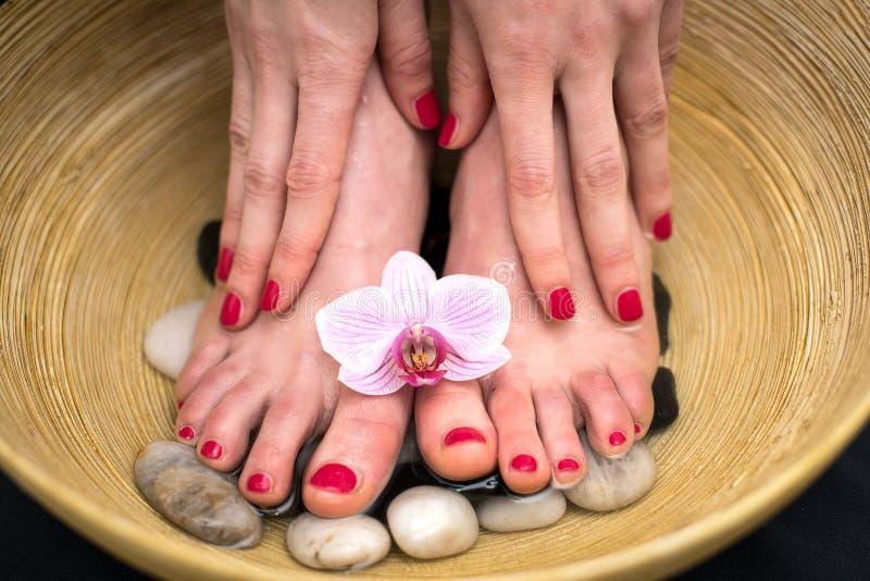 Weibliche Füße im Badekurort rollen mit Seesalz, Fußbad lizenzfreies stockbild