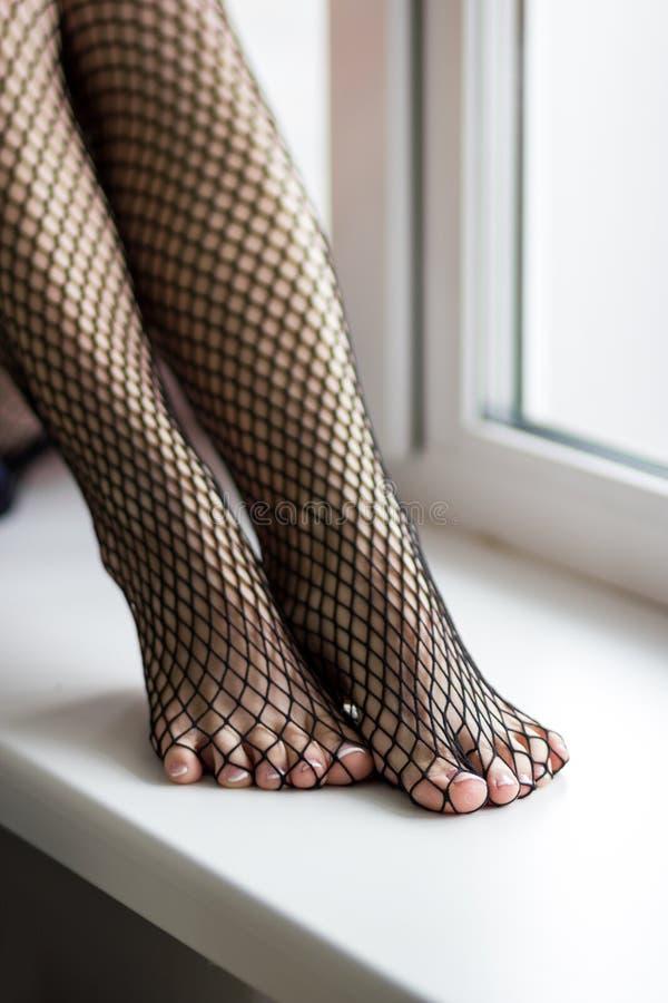 Weibliche Füße im schwarzen Fischnetz auf Fensterhintergrund lizenzfreie stockfotografie