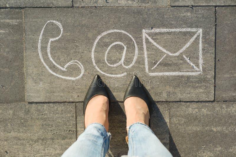 Weibliche Füße mit Kontaktsymbolen rufen die Post und Brief an, geschrieben auf grauem Bürgersteig, Kommunikation oder treten mit lizenzfreie stockfotos