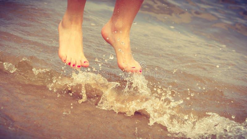 Weibliche Füße Sprung auf Strand stockfotos