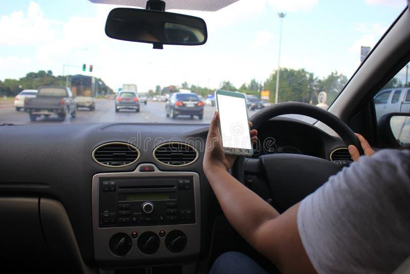 Weibliche Fahrerhände, welche auf der Autobahn die Autolenkplatte mit intelligentem Telefon des Holdingfreien raumes halten lizenzfreie stockbilder