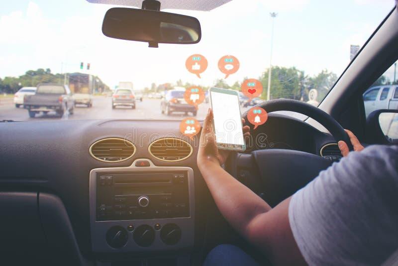 Weibliche Fahrerhände, welche die Autolenkplatte mit Holding Smartphone für die Prüfung des Social Media mit Ikone oder Hologramm stockfotos