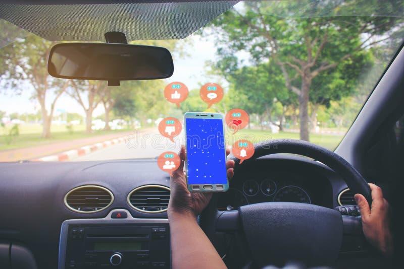 Weibliche Fahrerhände, welche die Autolenkplatte mit Holding Smartphone für die Prüfung des Social Media mit Ikone oder Hologramm lizenzfreie stockbilder
