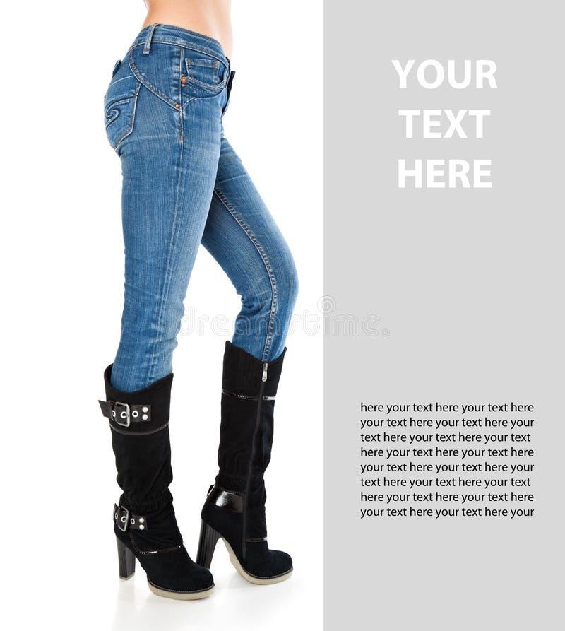 Weibliche Fahrwerkbeine in Blue Jeans und hohe Matten lizenzfreie stockfotos