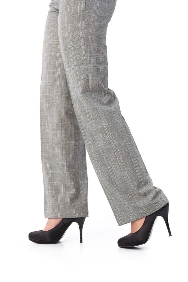 Weibliche Fahrwerkbeine in der Hose und in den hohen Absätzen lizenzfreie stockbilder