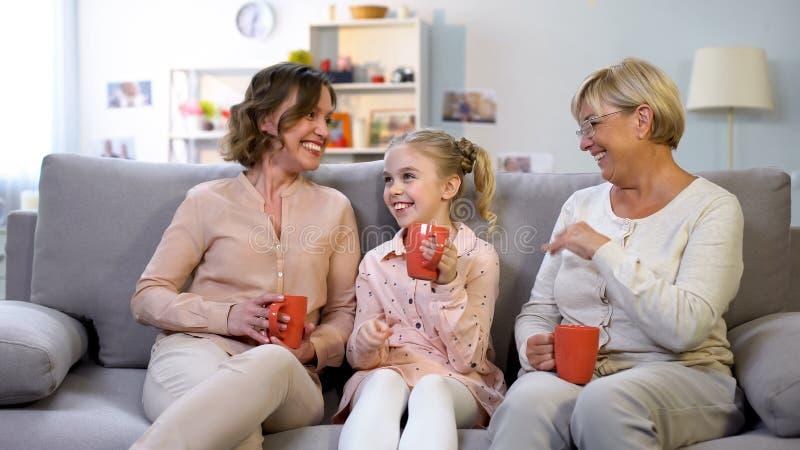 Weibliche Familienmitglieder, die, sitzend auf Sofa mit Schalen sich verständigen und lachen stockbild