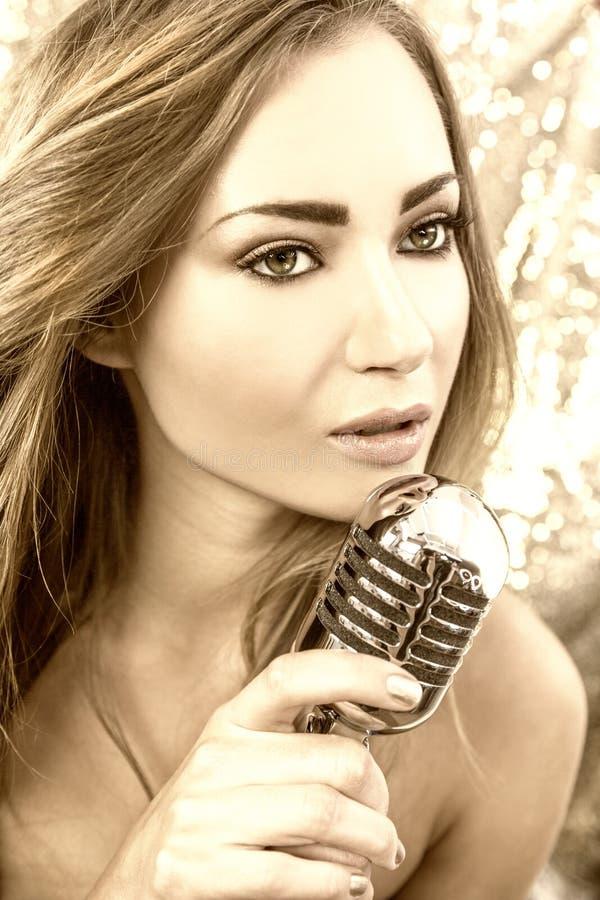 Weibliche Frau, die mit Weinlese-Mikrofon singt stockbilder