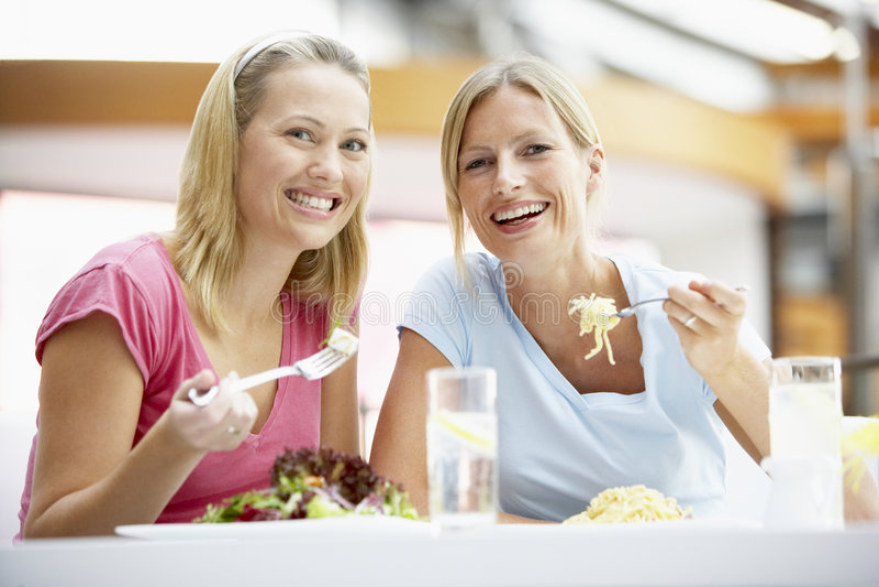 Weibliche Freunde, die zusammen am Mall zu Mittag essen lizenzfreies stockbild