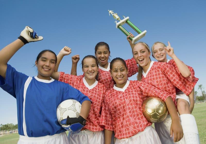 Weibliche Fußball-Spieler, die gewinnende Trophäe halten lizenzfreie stockfotos