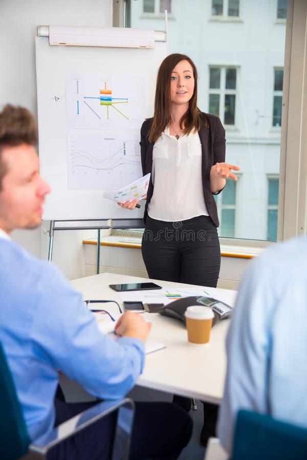 Weibliche gebende Berufsdarstellung zu den Kollegen lizenzfreie stockfotografie