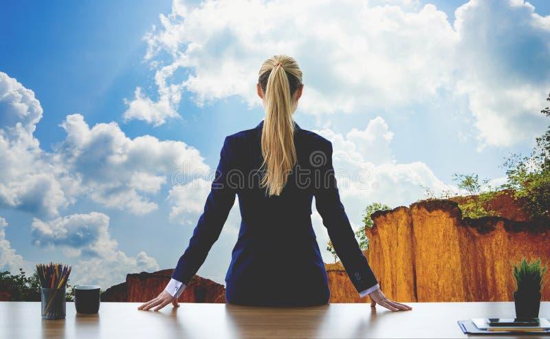 Weibliche Geschäftsfrau, die heraus den Fensterhimmelberg schaut lizenzfreie stockfotos
