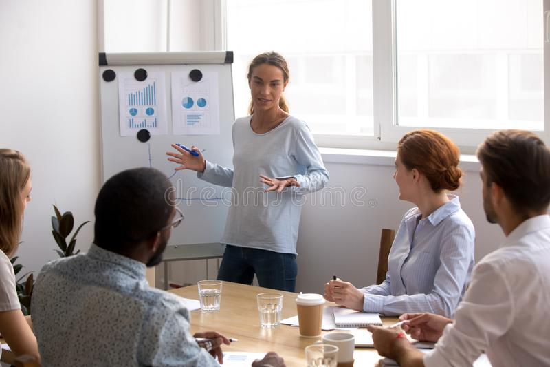 Weibliche Gesch?ftstrainerstellung nahe dem whiteboard, das mit verschiedenem Team spricht lizenzfreies stockbild