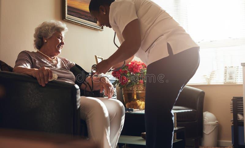Weibliche Gesundheitswesenarbeitskraft, die Blutdruck des älteren Patienten nimmt stockbild