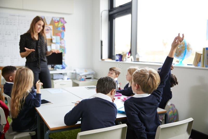 Weibliche Grundschullehrerstellung in einem Klassenzimmer, das zu den Schulkindern, sitzend an einem Tisch gestikuliert, der Händ lizenzfreies stockbild
