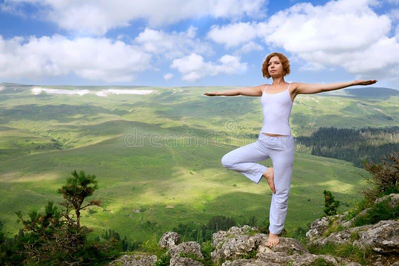 Weibliche Gymnastik auf dem Felsen lizenzfreie stockfotografie
