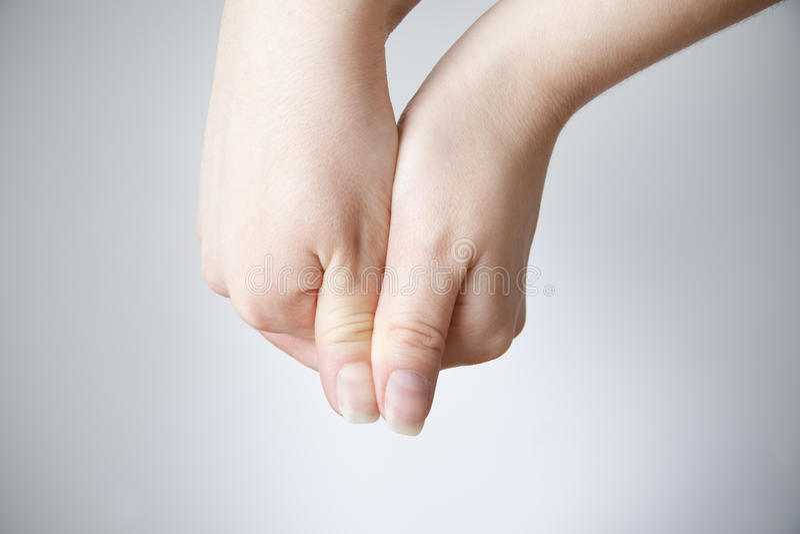 Weibliche Hände auf einem grauen Hintergrund stockbilder