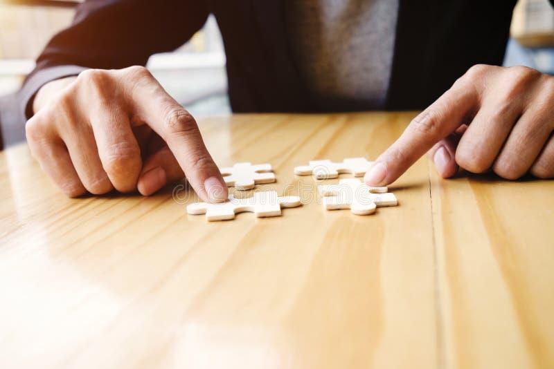 Weibliche Hände auf einem hölzernen Schreibtisch wählen Puzzlespiel aus stockfoto