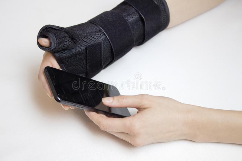 Weibliche Hände auf einem weißen Hintergrund Eine Hand in der Hand des Stabilisators an zweiter Stelle hält das Telefon lizenzfreie stockfotos