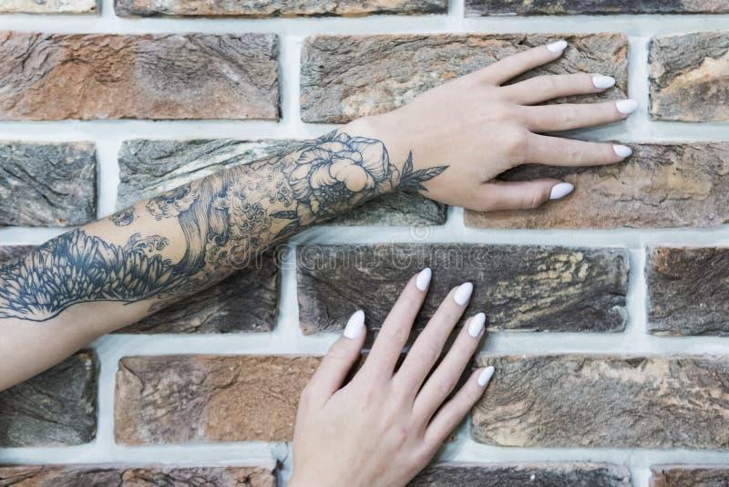 Weibliche Hände auf einer Backsteinmauer stockbilder