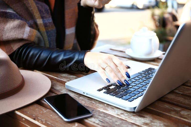 Weibliche Hände auf Laptopnotenauflage Frau, die mit Tasse Kaffee und Kuchen und Arbeiten sitzt Attraktives Modell unter Verwendu stockfotos