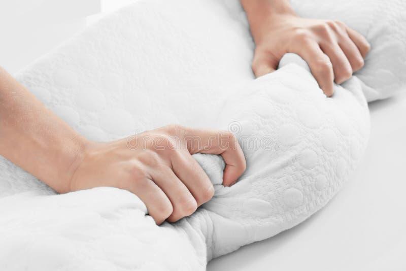 Weibliche Hände auf orthopädischem Kissen stockfotos