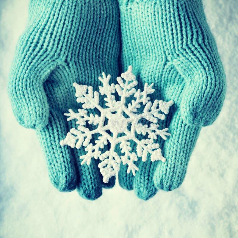 Weibliche Hände in der hellen Knickente strickten Handschuhe mit funkelnder wunderbarer Schneeflocke auf einem weißen Schnee Wint stockfoto