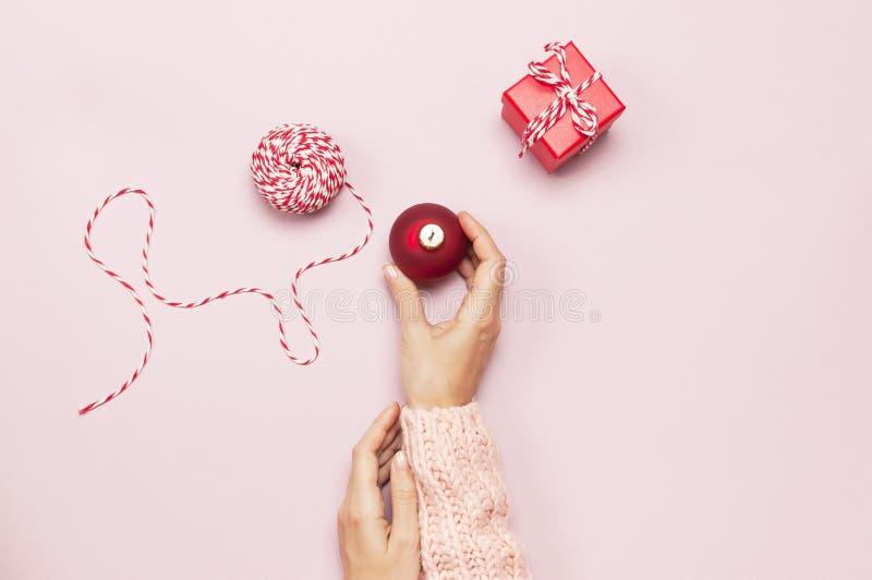 Weibliche Hände in der rosa gestrickten Strickjacke, die einen roten Weihnachtsball, Geschenkbox auf flacher gelegter Draufsicht  stockbild