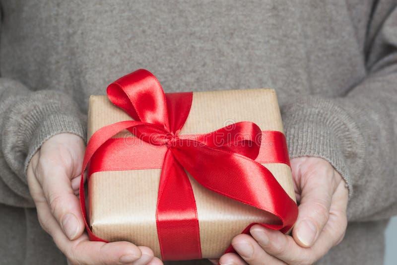 Weibliche Hände in der woolen beige Strickjacke, die beige Kasten eingewickelt im Kraftpapier mit rotem Band hält Abschluss oben stockbilder