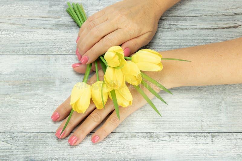 Weibliche Hände des Frauenrosas manikürten auf Nägeln mit einem Blumenstrauß von stockbild