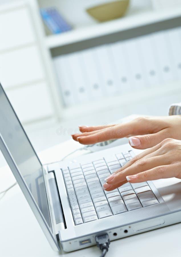 Weibliche Hände, die auf Tastatur schreiben stockbild