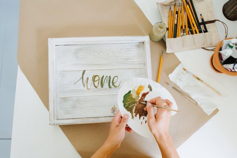 Weibliche Hände, die Buchstaben mit Farbe auf einem hölzernen weißen Behälter zeichnen lizenzfreie stockfotos