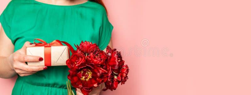 Weibliche Hände, die ein Geschenk als Überraschungsgeschenk und einen Blumenstrauß von roten Blumen halten stockbild