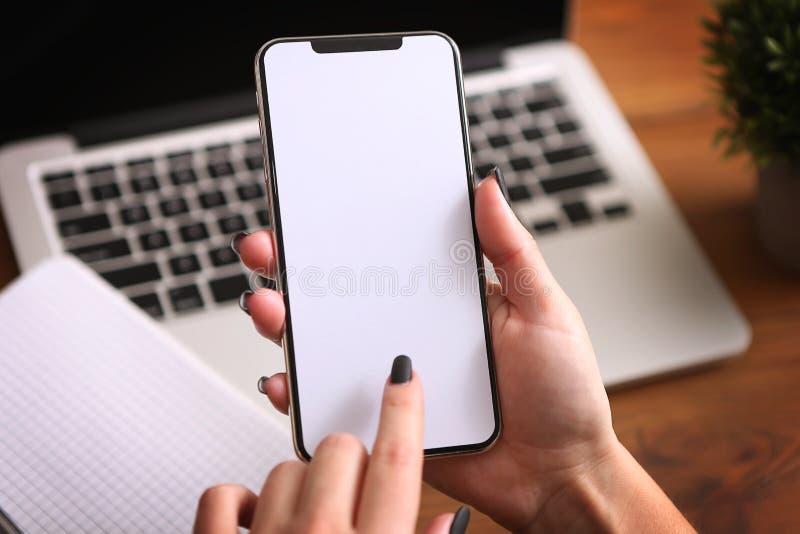 Weibliche Hände, die ein weißes Telefon mit lokalisiertem Schirm auf einer Tabelle mit Laptop halten lizenzfreie stockfotos