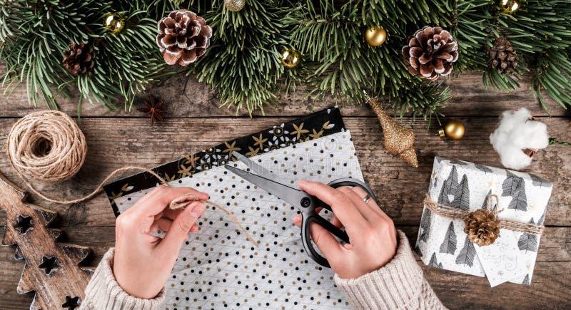 Weibliche Hände, die ein Weihnachtsgeschenk am Feiertag einwickelt auf rustikalem Hintergrund mit Tannenzweigen, Golddekorationen lizenzfreie stockfotos