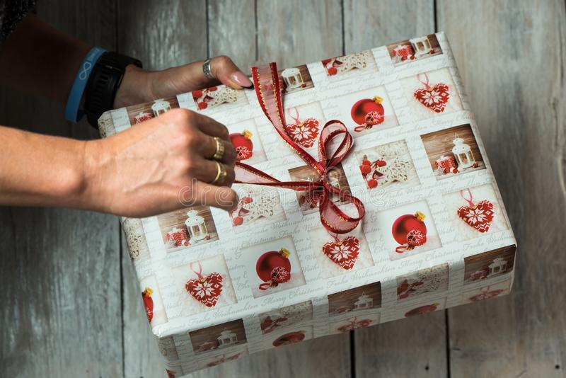 Weibliche Hände, die ein Weihnachtsgeschenk halten stockbild
