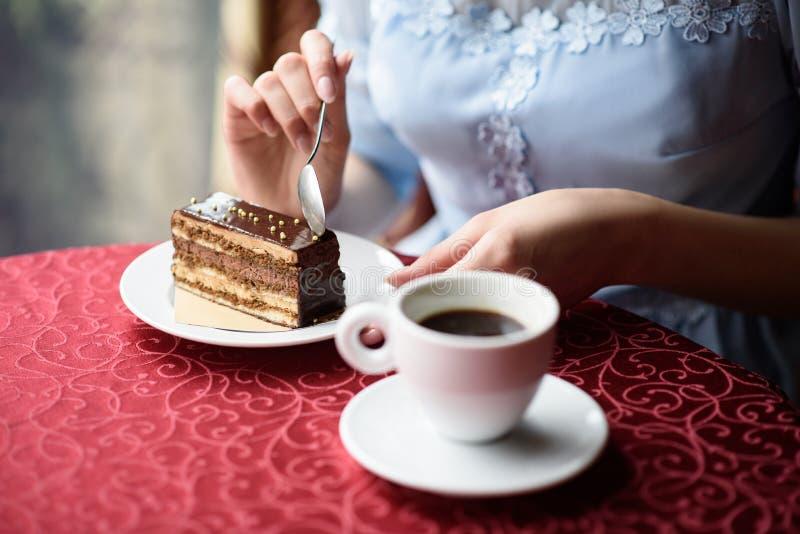 Weibliche Hände, die einen Teelöffel halten und ein Stück des Schokoladenkuchens abschneiden lizenzfreie stockbilder