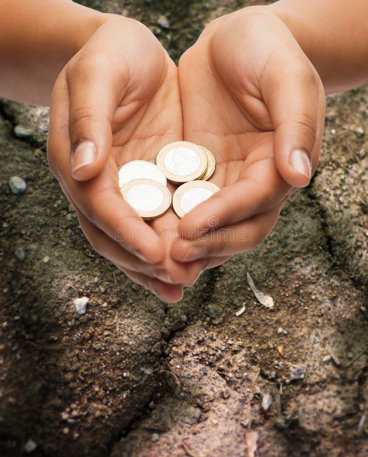 Weibliche Hände, die Euromünzen über Boden halten stockbild