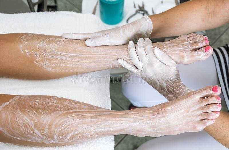 Weibliche Hände, die Füße mit befeuchtender Sahne behandeln lizenzfreie stockfotos