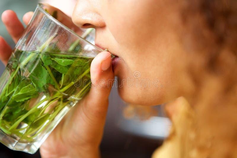Weibliche Hände, die Glas tadellosen Tee zum Mund halten lizenzfreie stockbilder