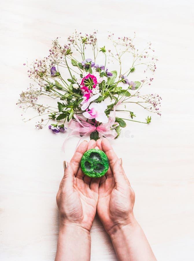 Weibliche Hände, die grüne handgemachte Seife auf weißem Hintergrund mit Anlagen und Blumen, Draufsicht halten lizenzfreie stockfotografie